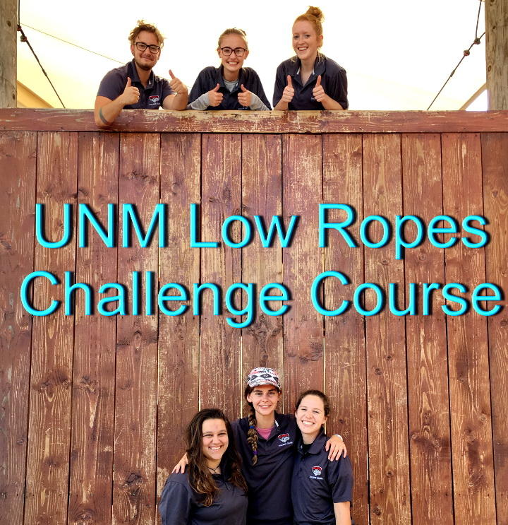 "a photo of the LRCC staff, three of whom are at the top of the Team Wall giving thumbs up, the other three are at the bottom smiling. Blue overlaid text reads ""UNM Low Ropes Challenge Course."""